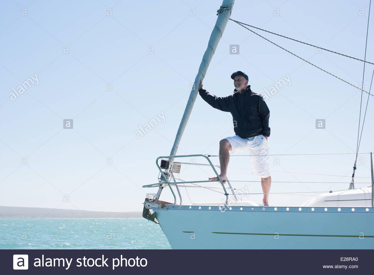 Uomo in piedi sul ponte della barca a vela Immagini Stock