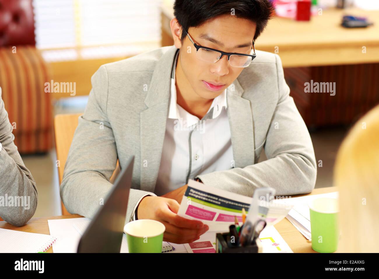 Imprenditore asiatici in bicchieri di sedere a tavola e istruzioni per la lettura in office Immagini Stock