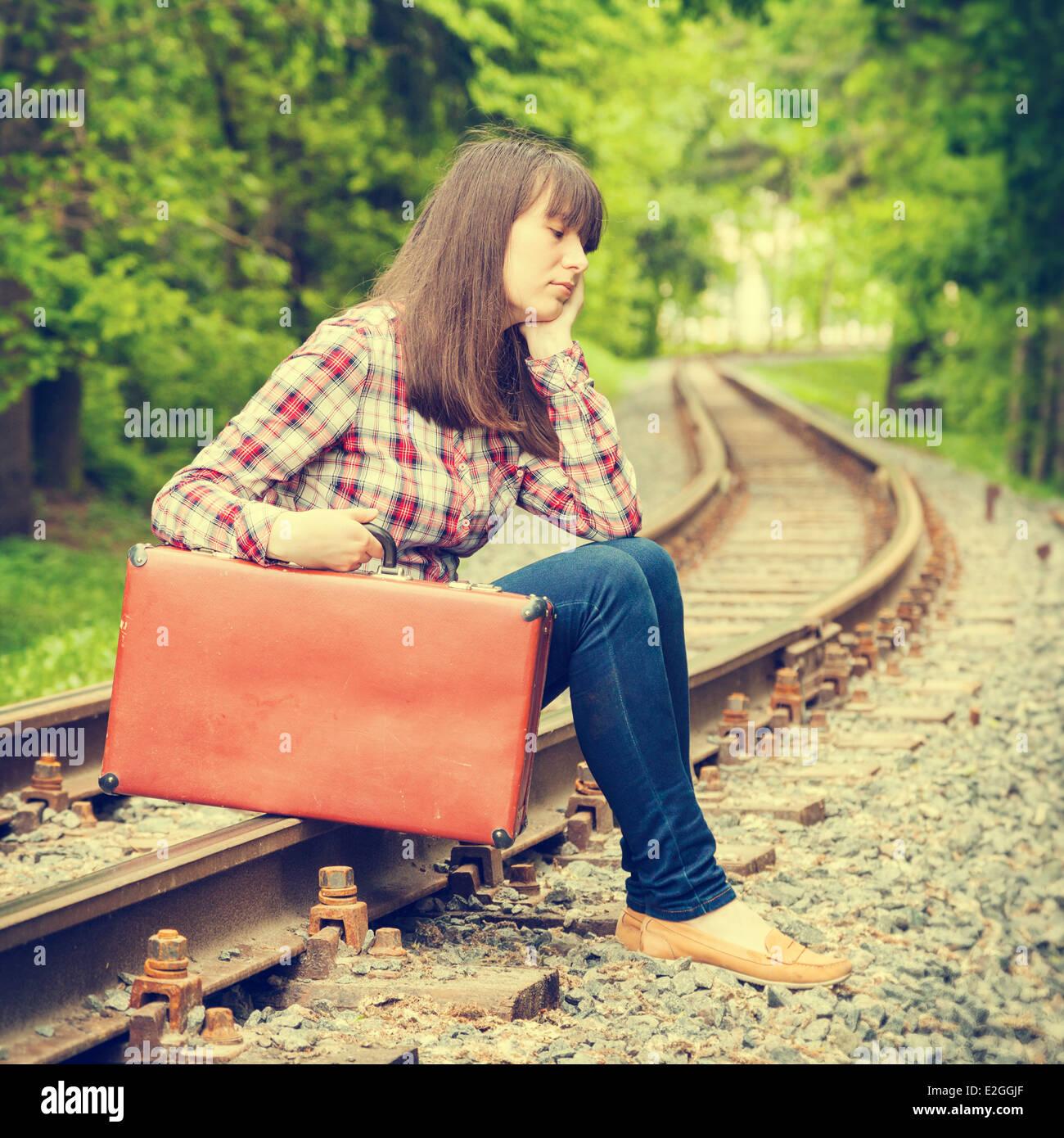 Adolescente ragazza triste con la valigia seduto su rotaie Immagini Stock
