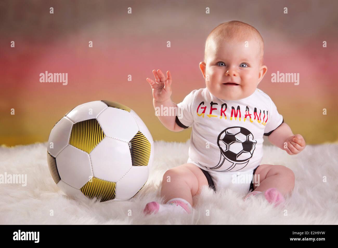 Baby girl, 7 mesi, indossando una Germania football jersey con un calcio, colori tedesco sul retro Immagini Stock