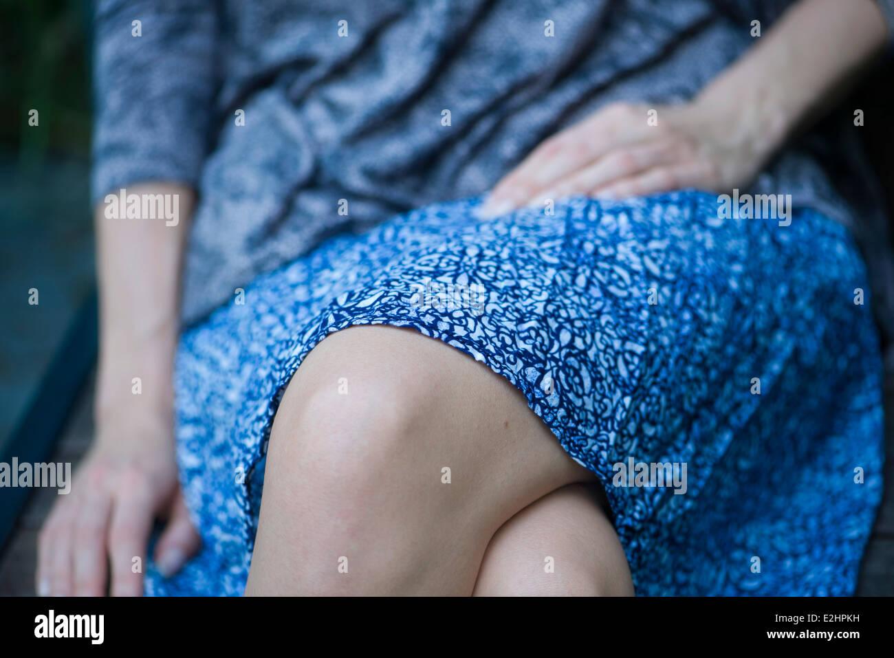 Donna seduta con le gambe incrociate, ritagliato Foto Stock