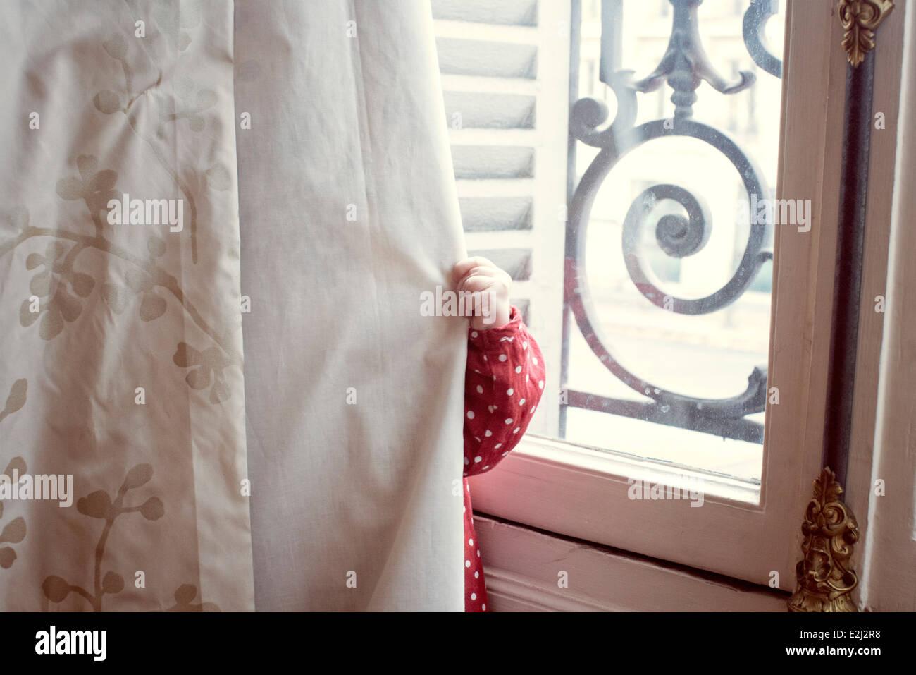 Bambino nascondere dietro la cortina Immagini Stock