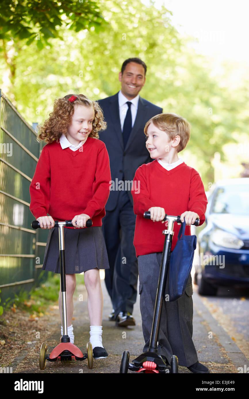 Equitazione per bambini scooter sul loro modo a scuola con il Padre Immagini Stock