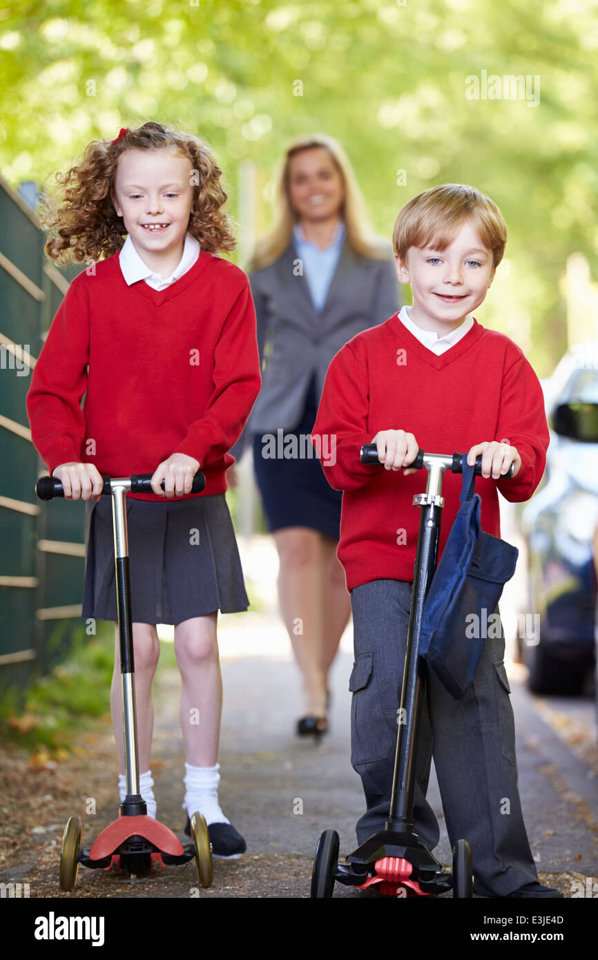 Equitazione per bambini scooter sul loro modo a scuola con la madre Immagini Stock