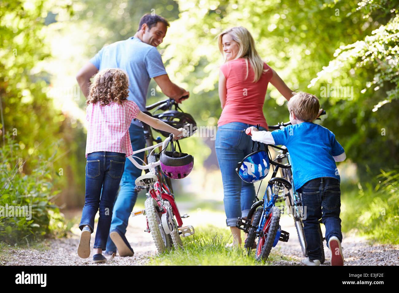 Famiglia spingendo le moto lungo il paese via Immagini Stock