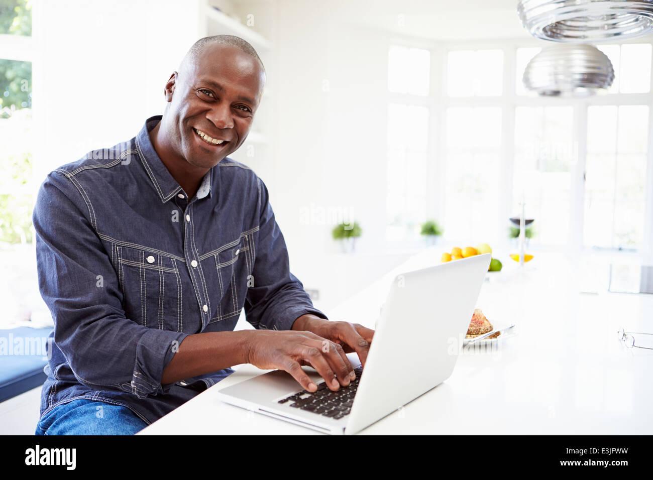 African American uomo utilizzando portatile a casa Foto Stock