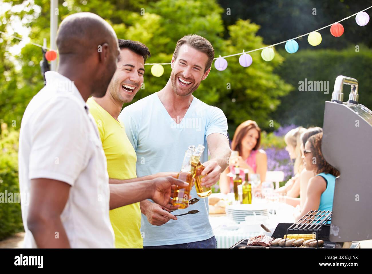 Un gruppo di uomini la cottura su barbecue a casa Immagini Stock