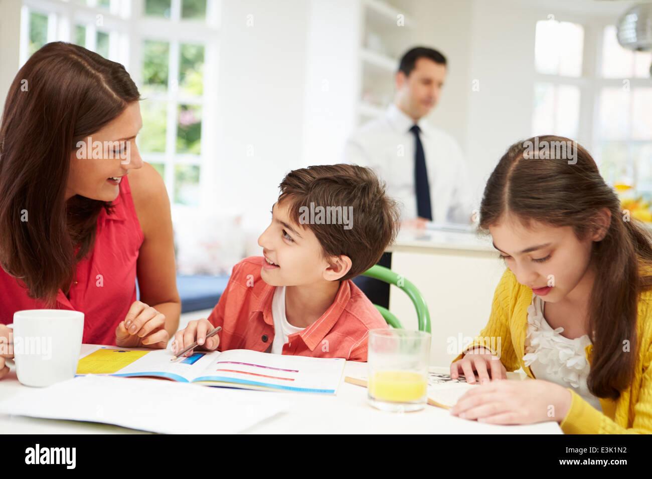 La mamma aiuta i bambini con i compiti come papà lavora in background Immagini Stock