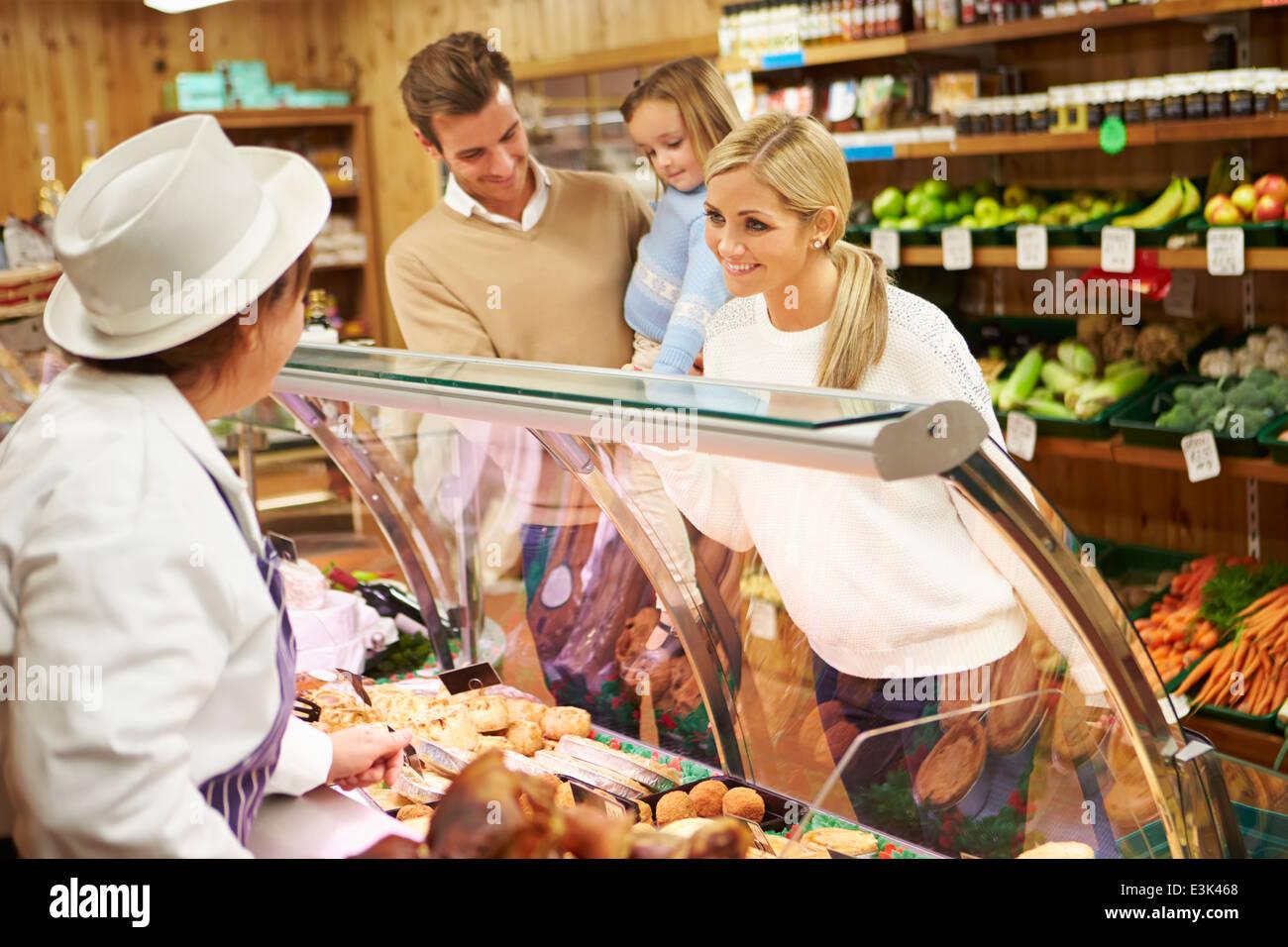 Femmina assistente di vendita di servire la famiglia in negozio di specialità gastronomiche Foto Stock