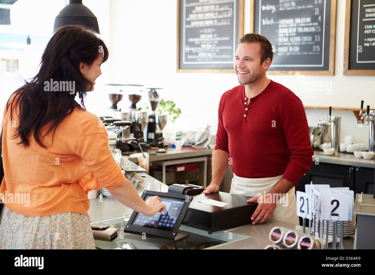 Il cliente di pagare in Coffee Shop mediante schermo tattile Foto Stock