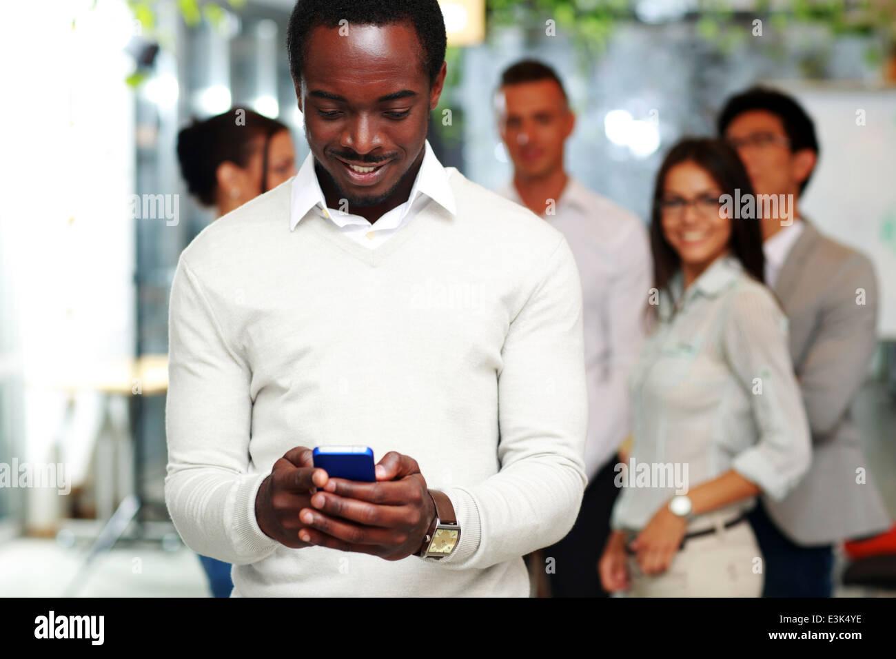 Happy businessman utilizza lo smartphone di fronte ai colleghi Immagini Stock