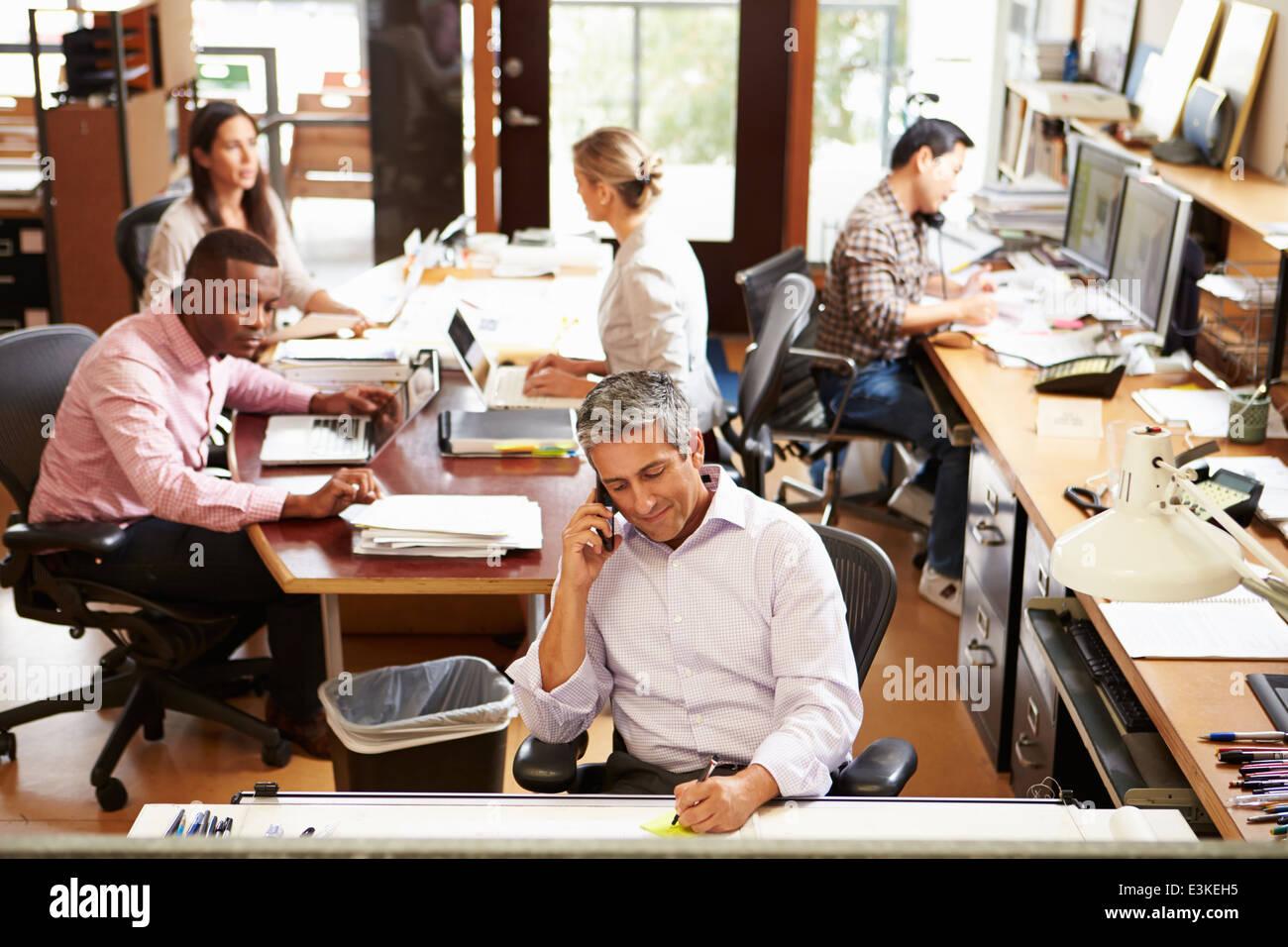 Interno occupato di ufficio dell'architetto con personale che lavora Immagini Stock