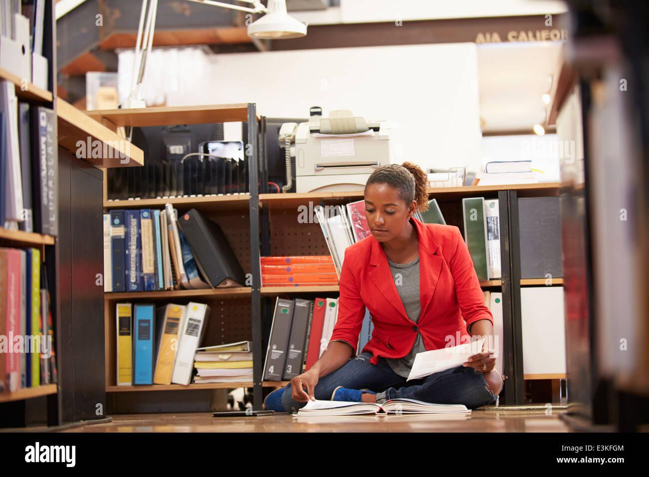 Imprenditrice seduta sul pavimento di Office la lettura dei documenti Immagini Stock