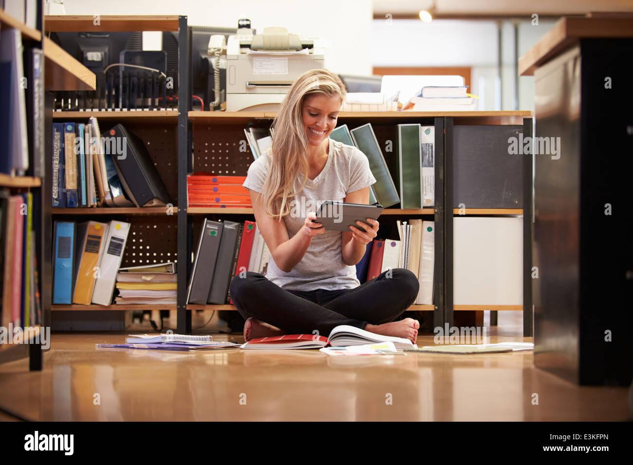 Imprenditrice seduta sul pavimento di Office con tavoletta digitale Immagini Stock
