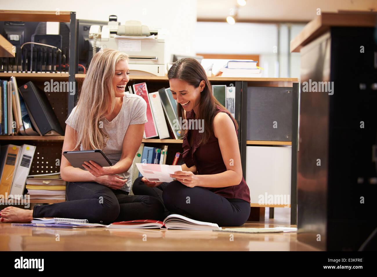 Due imprenditrici sedersi sul pavimento per ufficio con tavoletta digitale Immagini Stock