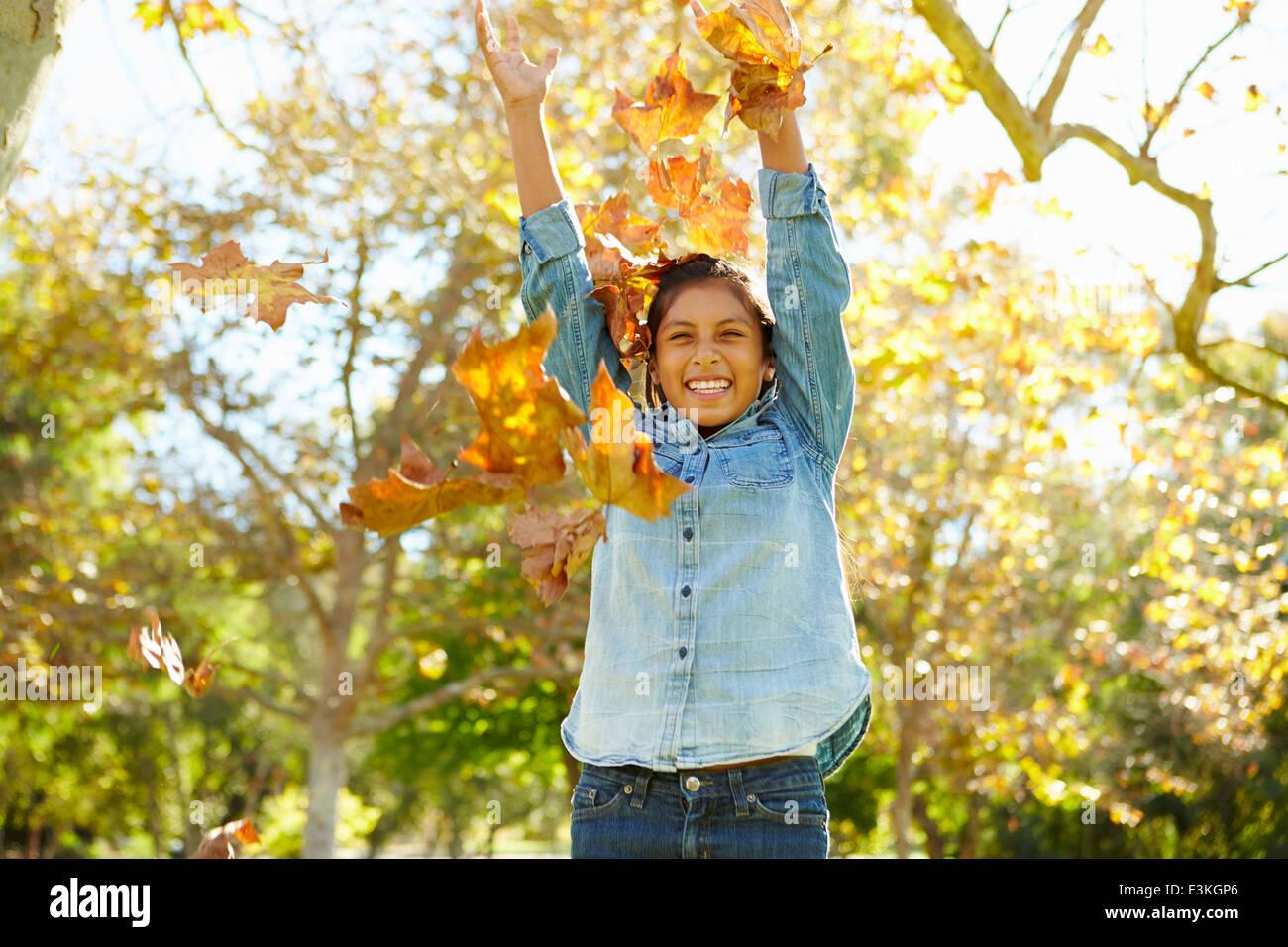 Giovane ragazza gettando le foglie di autunno in aria Immagini Stock