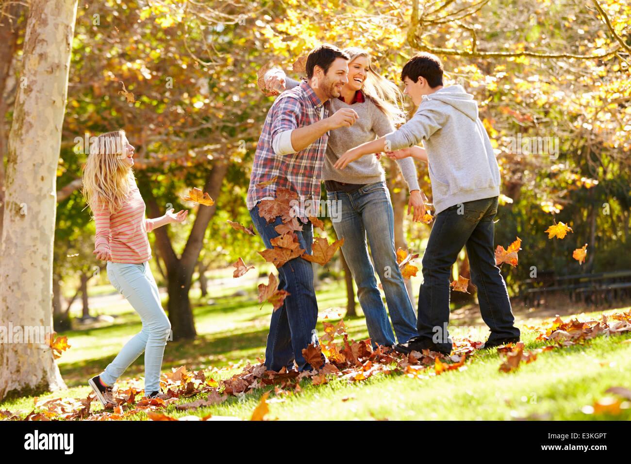 Famiglia di gettare le foglie di autunno in aria Immagini Stock