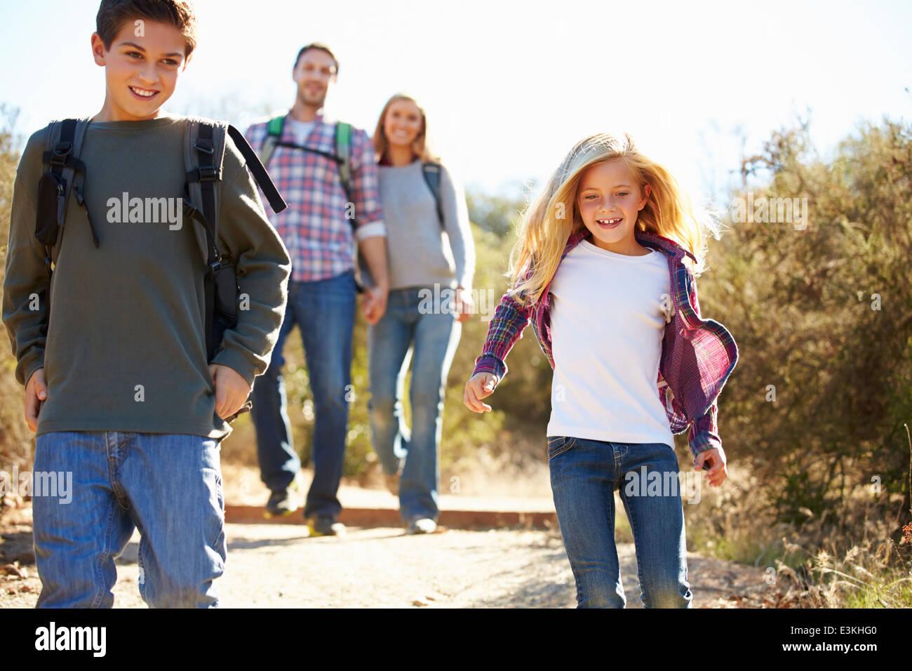 Madre e bambini escursioni in campagna indossando zaini Foto Stock