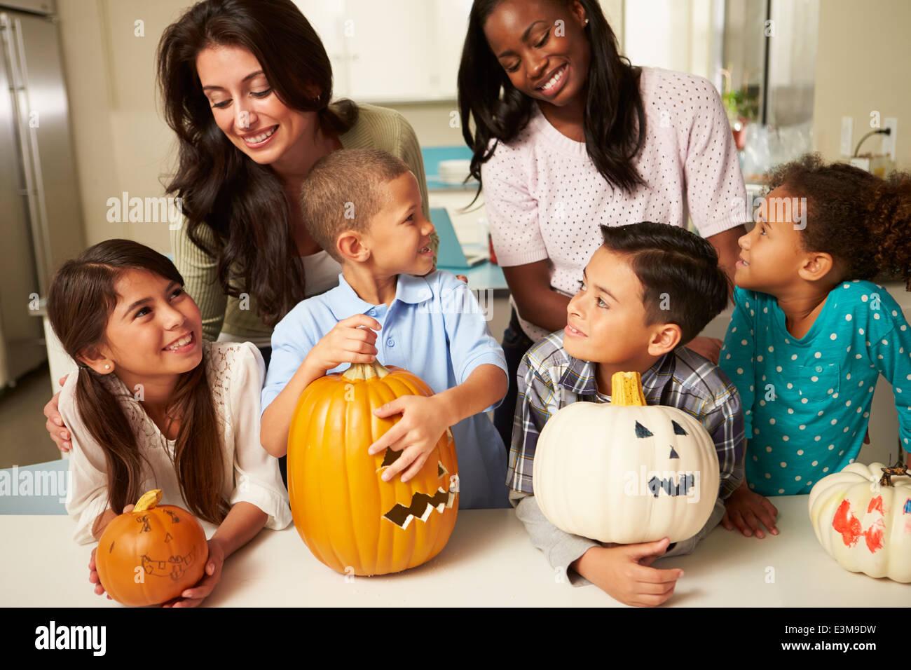 Le madri e i bambini rendendo lanterne di Halloween Foto Stock