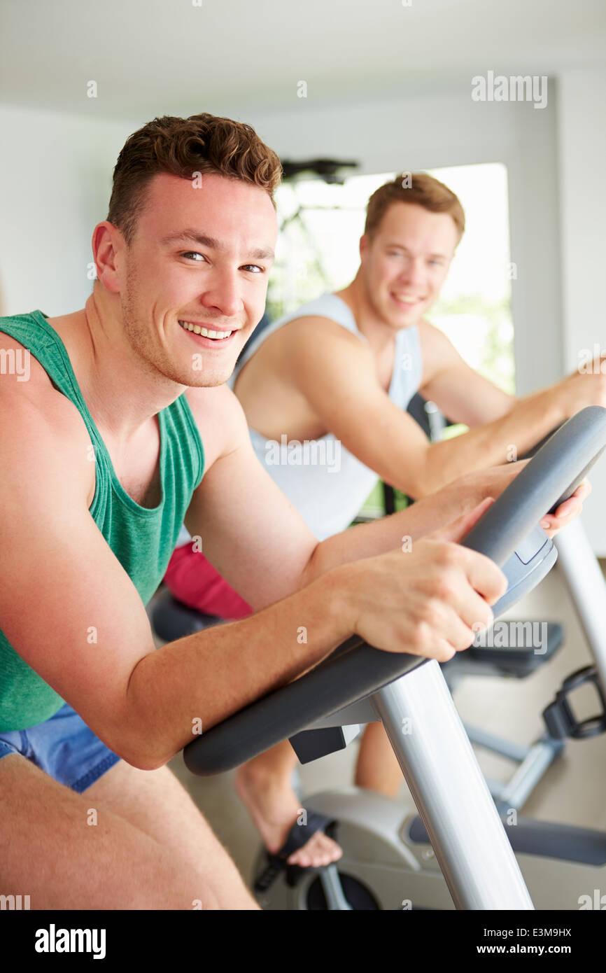 Due giovani uomini la formazione in palestra sulle macchine in bicicletta insieme Immagini Stock