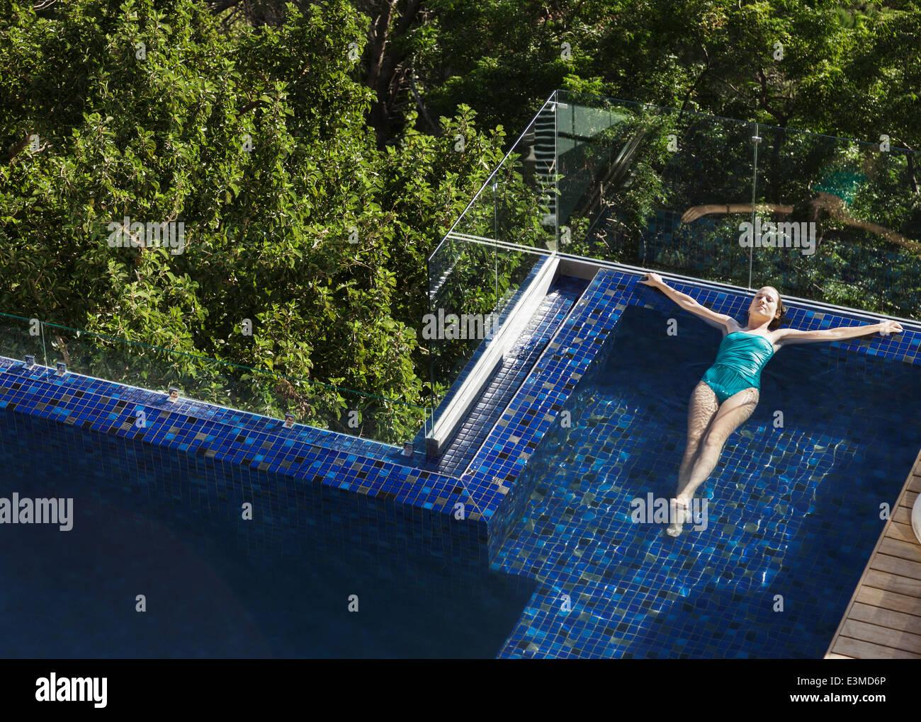 Donna galleggianti in piscina di lusso Immagini Stock