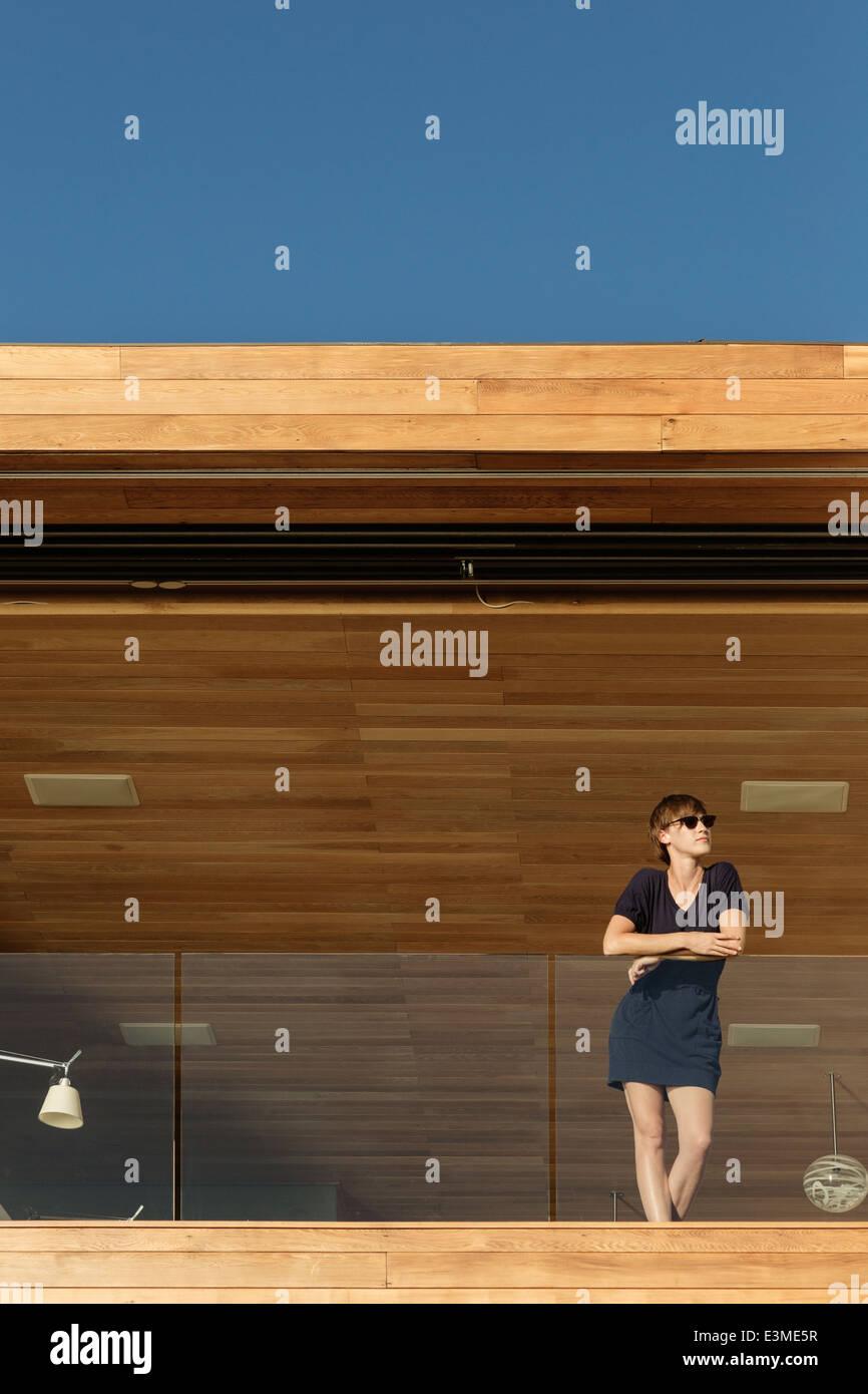 Donna in piedi sul balcone di lusso Immagini Stock