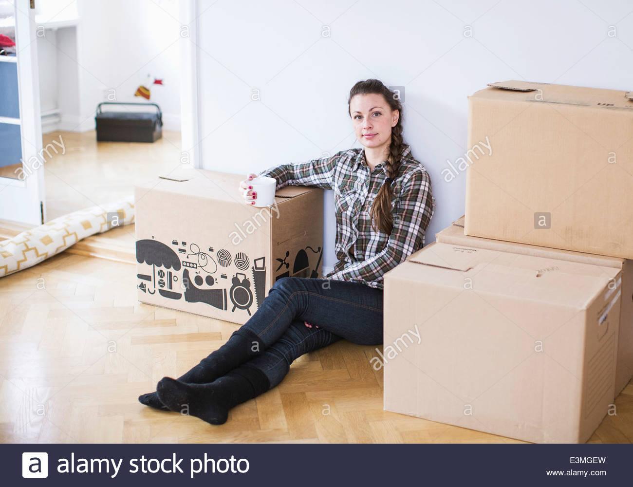 A piena lunghezza Ritratto di giovane donna con caffè nella nuova casa Immagini Stock