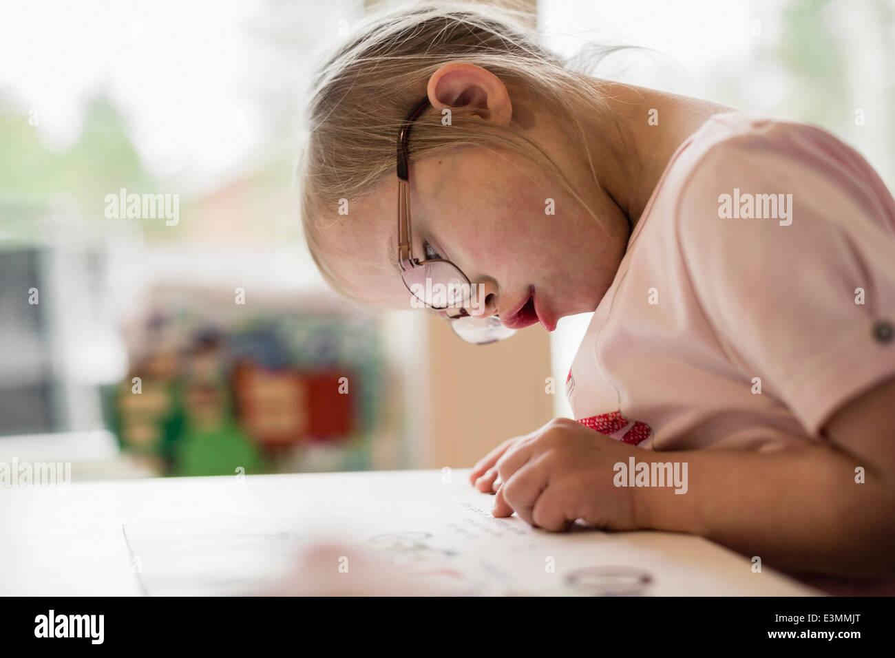 La ragazza con la sindrome di down che studiano a tavola Immagini Stock