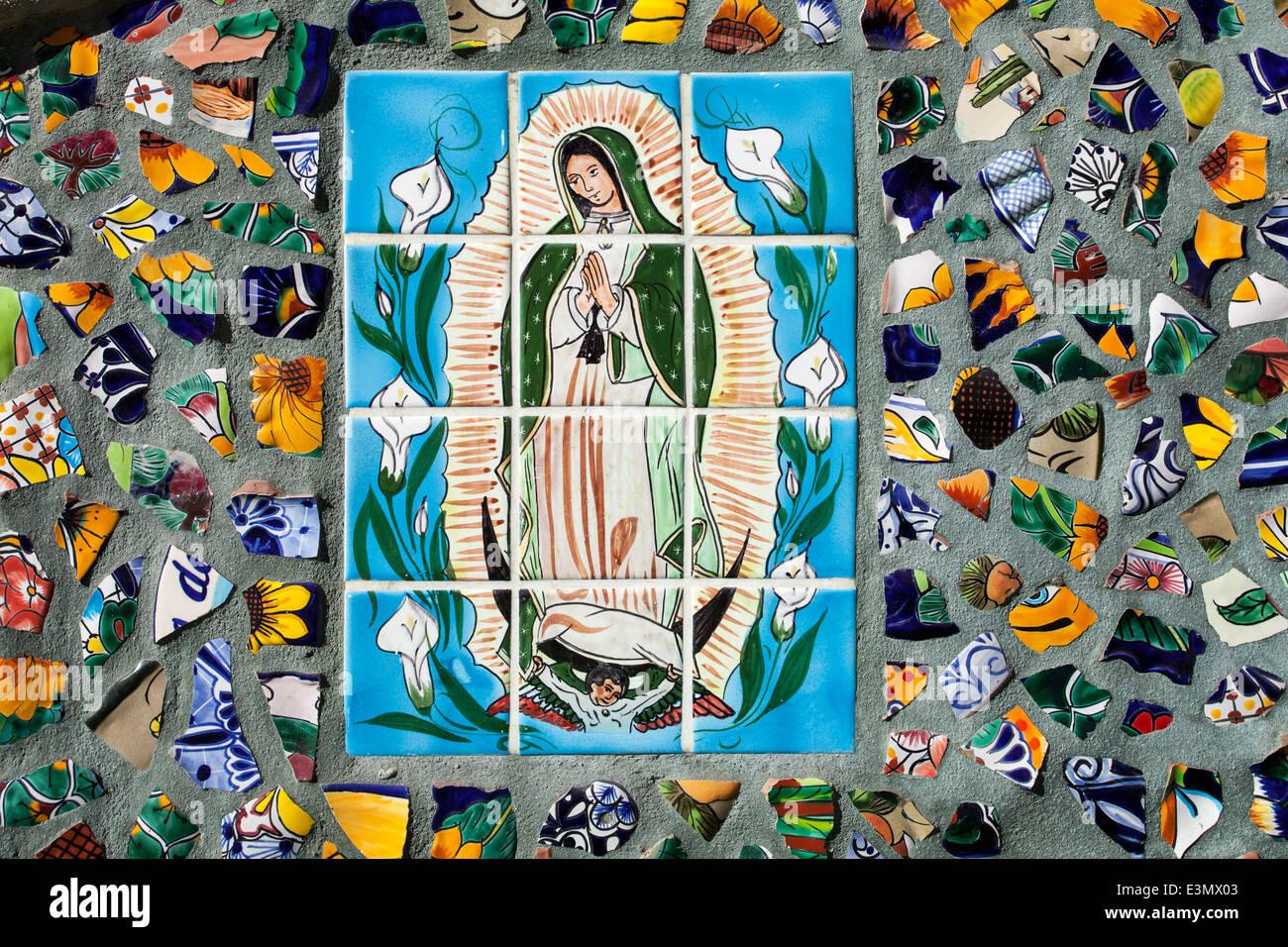 Una piastrella la pittura della Vergine di gualalupe circondato da pezzi rotti di tile set in cemento, Puerto Vallarta, Immagini Stock