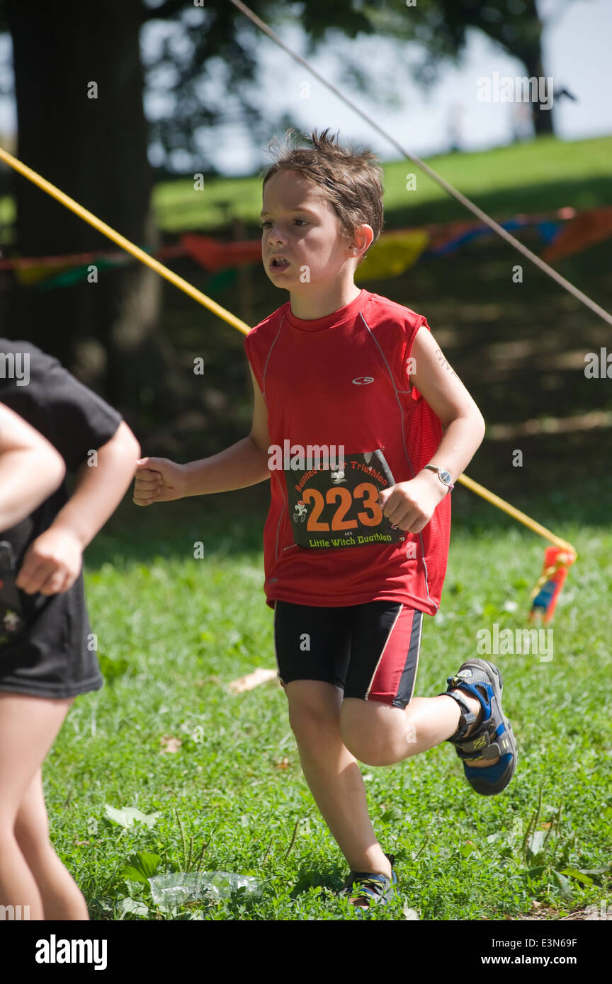 Sox (6) anno vecchio ragazzo viene eseguito come egli partecipa nella città infestata Jr. Triathlon in Salem MA Foto Stock