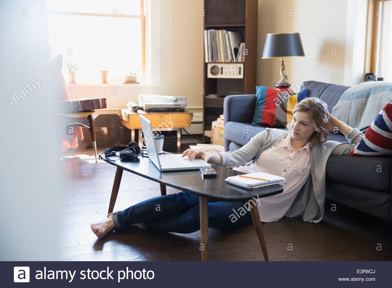Donna che utilizza sul computer portatile sul soggiorno piano Immagini Stock