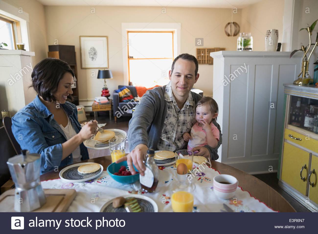 Giovane famiglia gustando la prima colazione a tavolo da pranzo Foto Stock