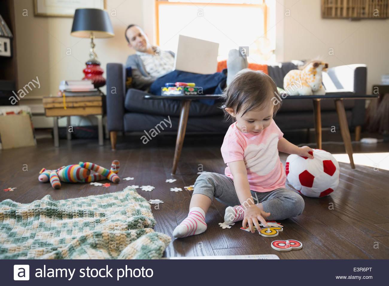 Padre con il computer portatile guarda la bambina gioca Immagini Stock