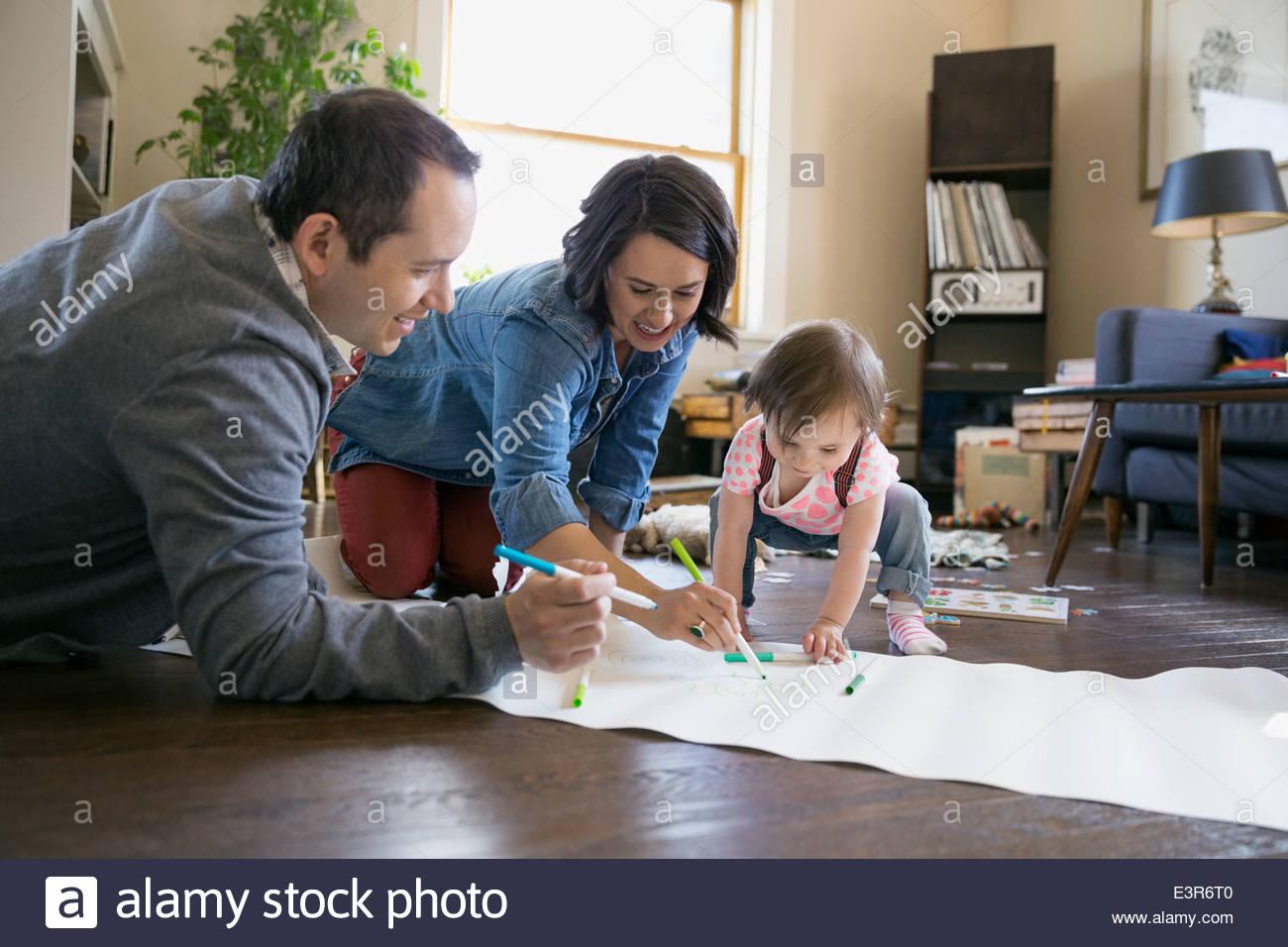 Famiglia giovane disegno in salotto Immagini Stock