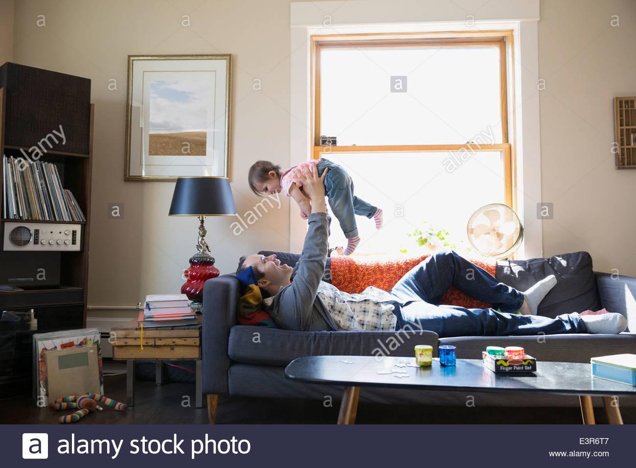 Il padre del bambino di sollevamento figlia overhead sul divano Immagini Stock
