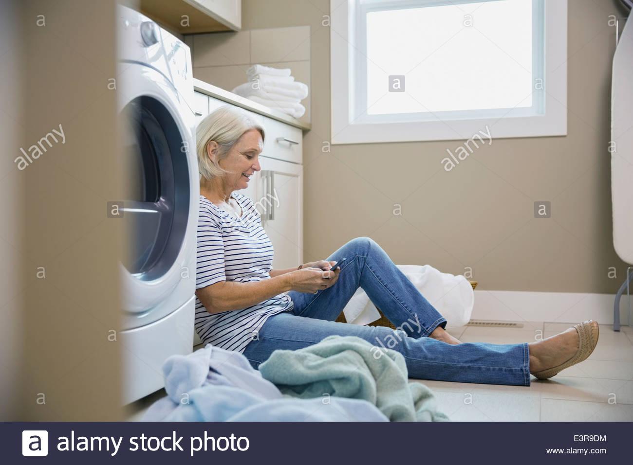 Donna texting sul servizio lavanderia il pavimento della camera Immagini Stock