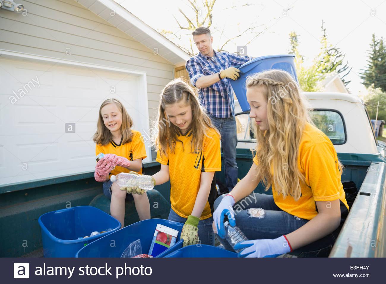 Ragazze in uniformi di riciclaggio di smistamento nel letto del carrello Immagini Stock