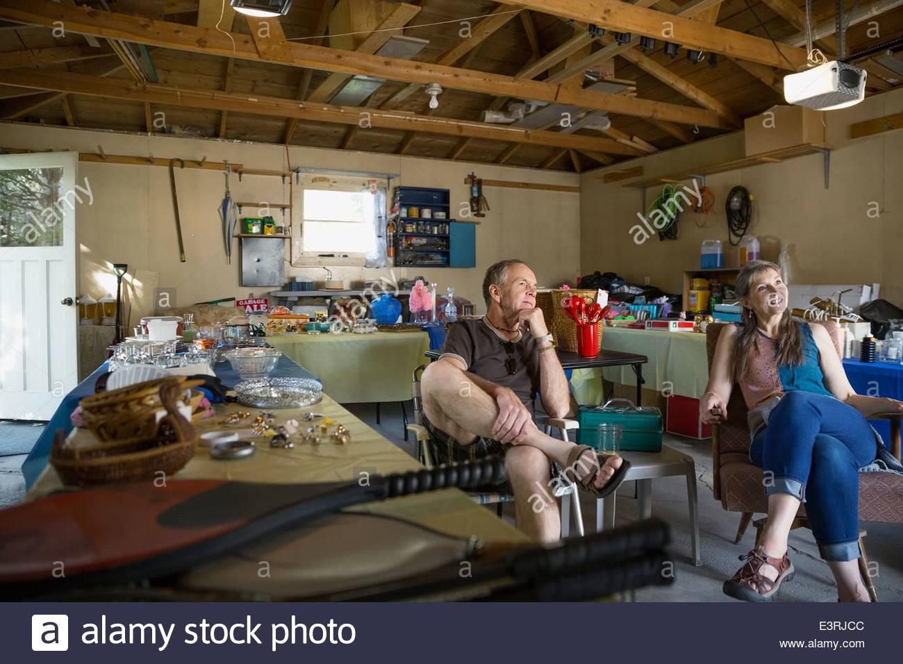 Giovane seduto alla vendita di garage Immagini Stock