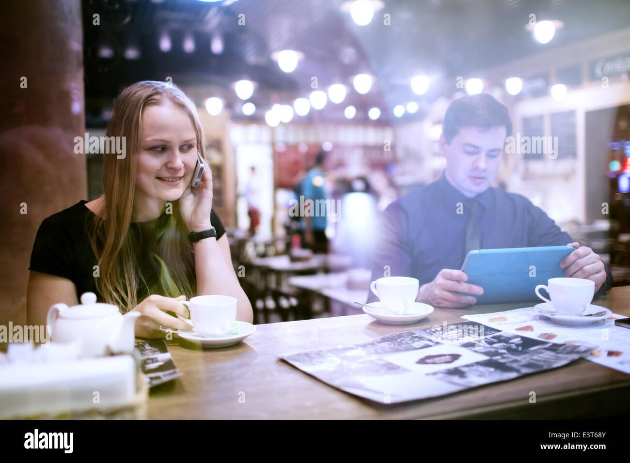 Donna sul cellulare di bere il caffè Immagini Stock