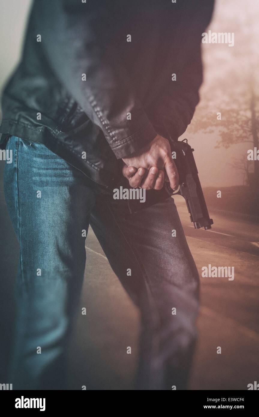 Uomo in possesso di una pistola Foto Stock