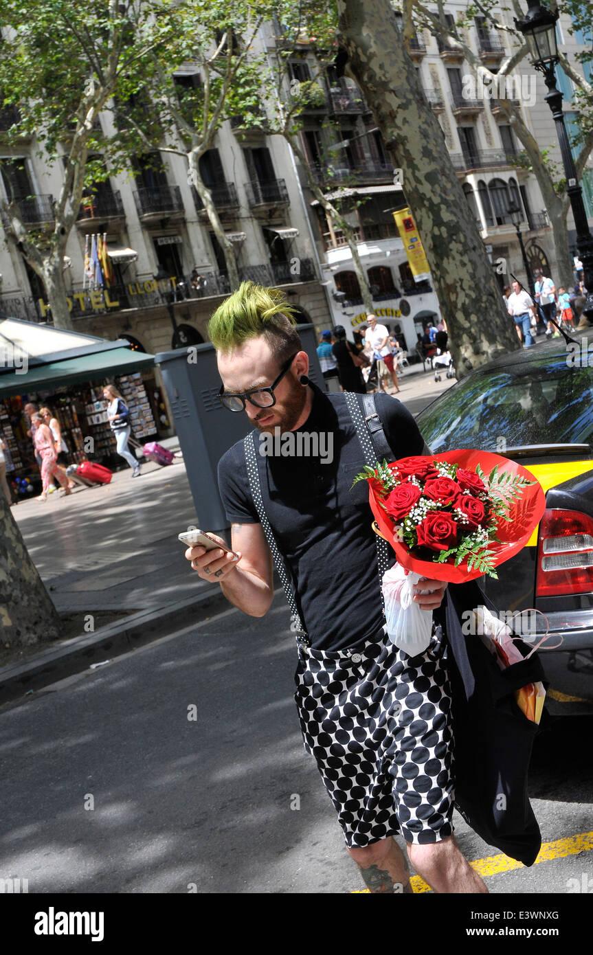 Modern boy con fiori in attesa di un taxi e controllare i suoi mobili in Las Ramblas di Barcellona Immagini Stock