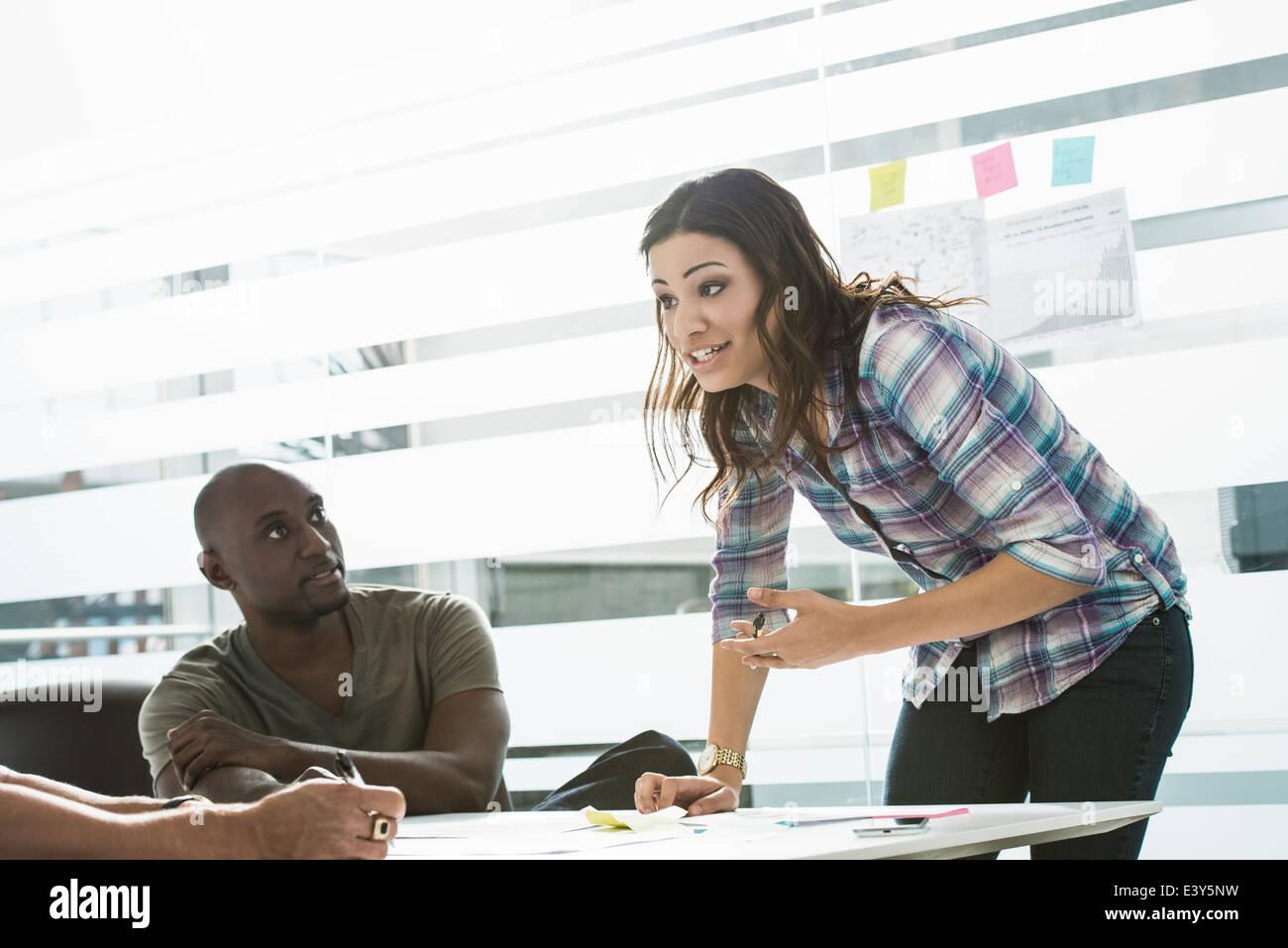 Imprenditrice spiegando le idee ai colleghi di sesso maschile in office Immagini Stock
