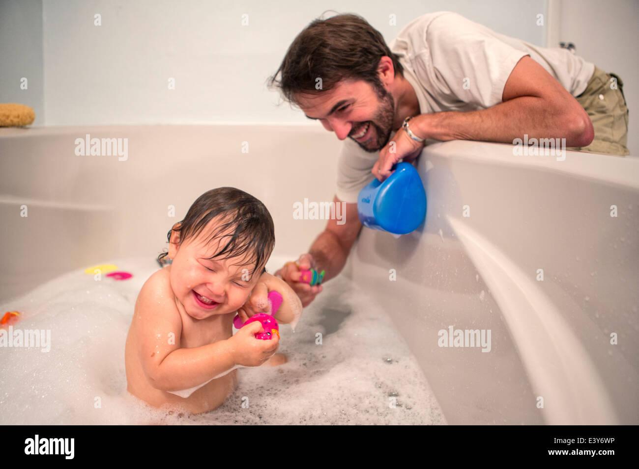 Padre e figlia toddler giocando al momento in bagno Immagini Stock