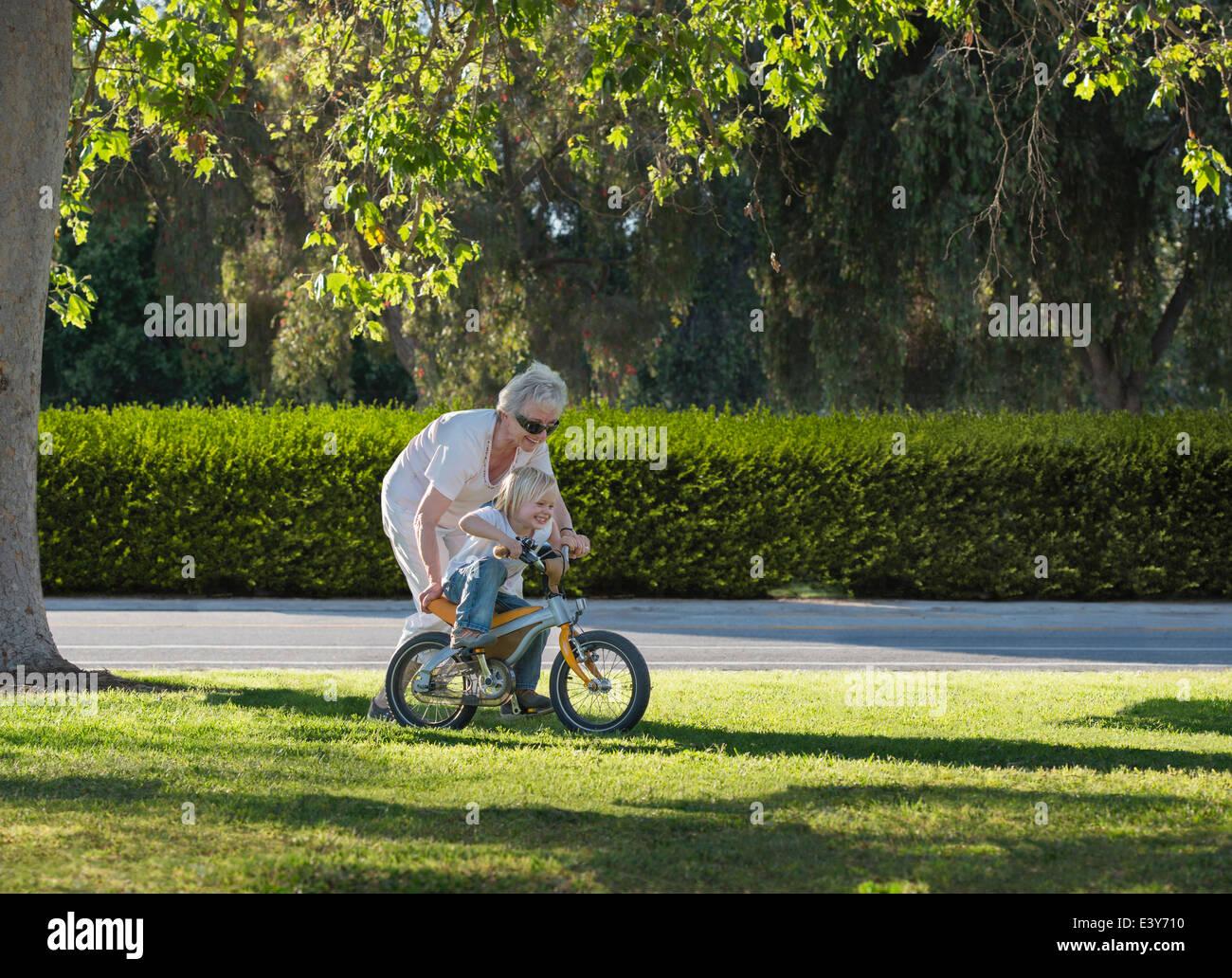 Tre anni di apprendimento del ragazzo al ciclo con la nonna in posizione di parcheggio Immagini Stock