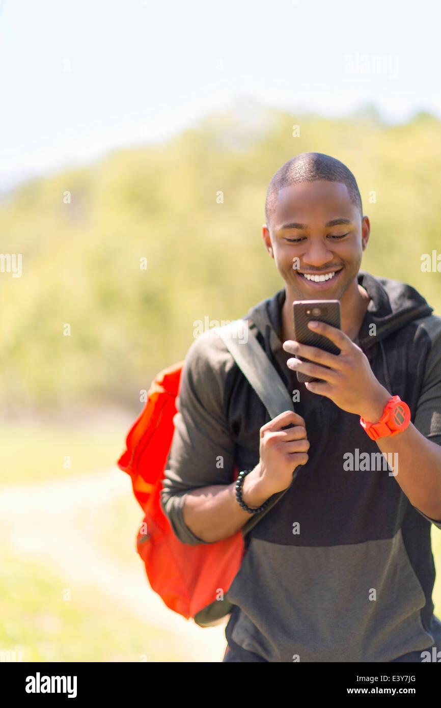 Giovane maschio escursionista lettura messaggio sullo smartphone Foto Stock