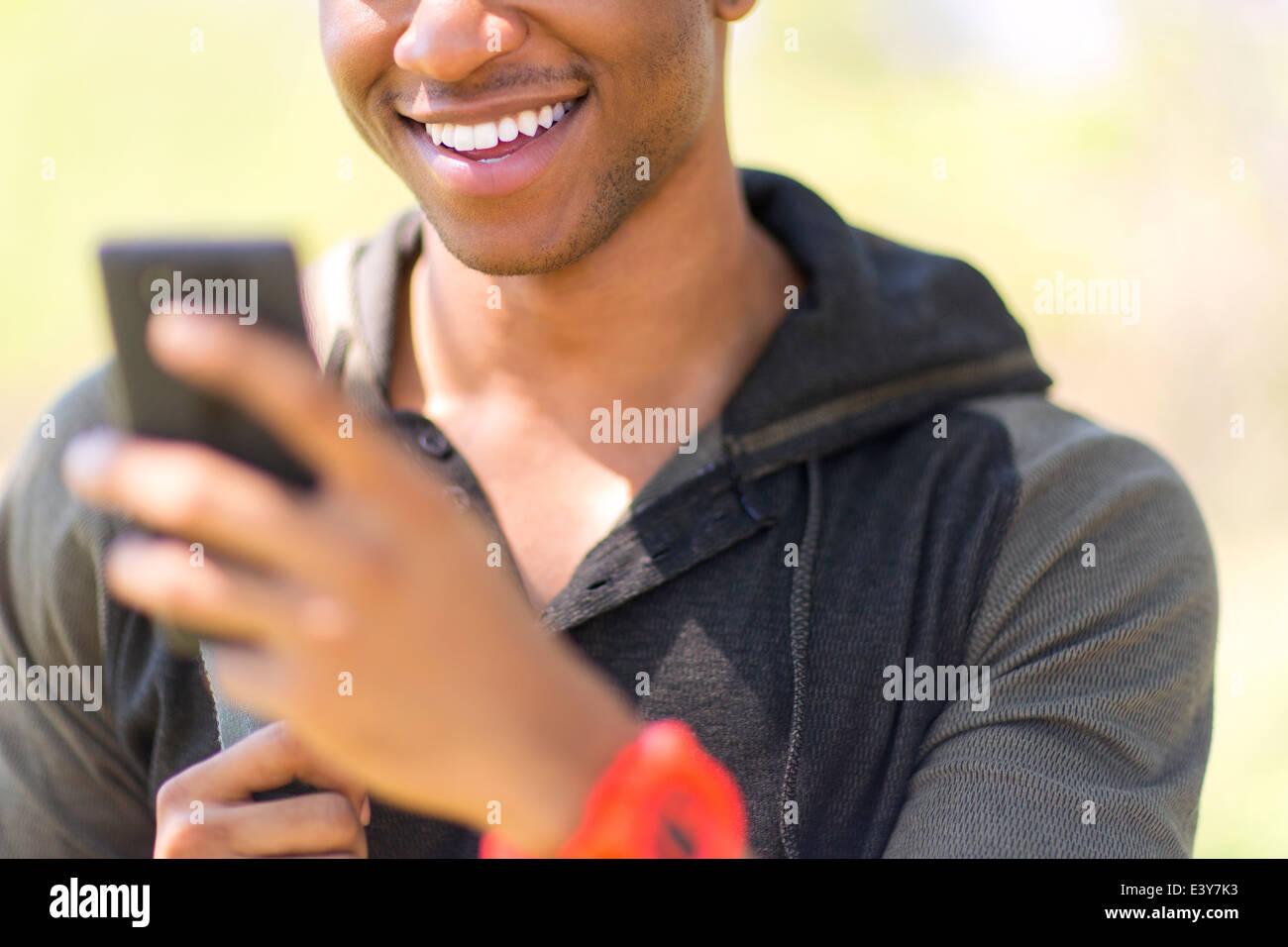 Chiusura del giovane maschio escursionista guardando smartphone Immagini Stock