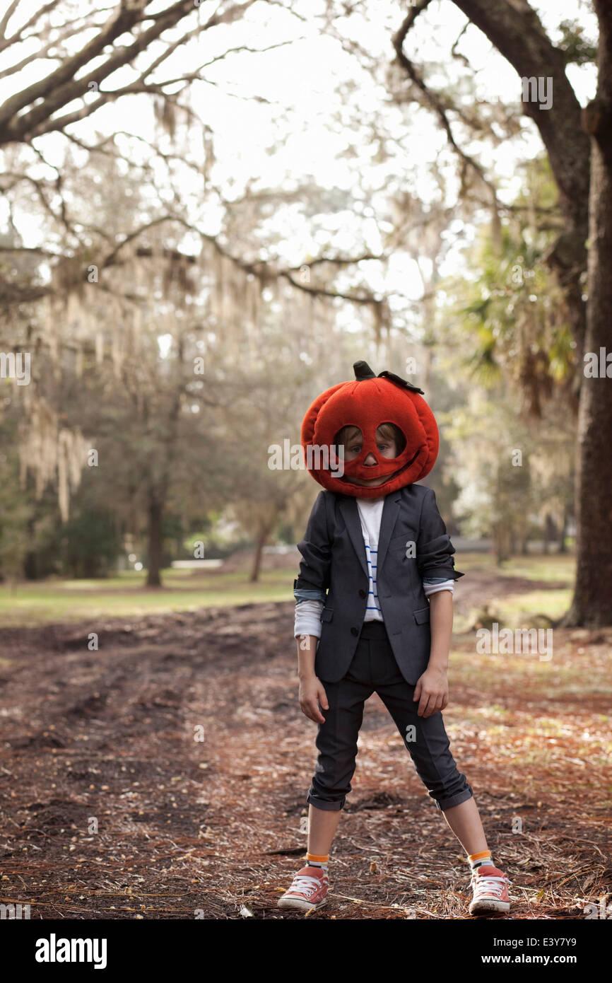 Ritratto di ragazzo nella foresta che indossa la testa di zucca Immagini Stock