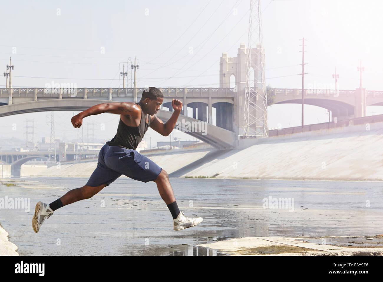 Giovane uomo velocità correre e saltare da riverbank Immagini Stock