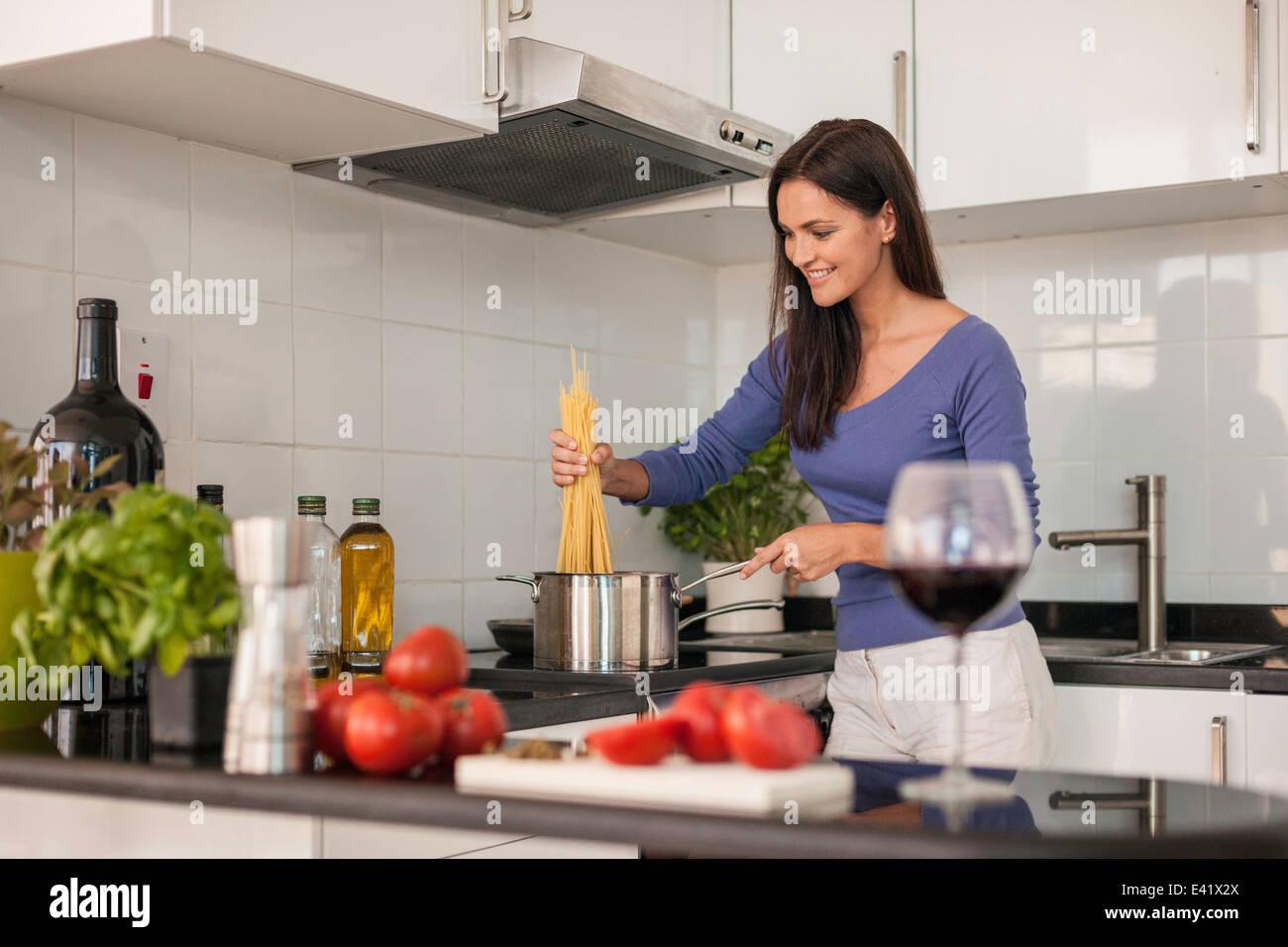 Giovane donna cucinare gli spaghetti in cucina Immagini Stock