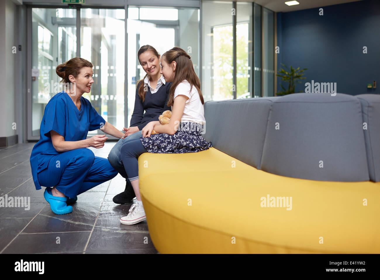 Infermiere parlando a ragazza in ospedale in sala d'attesa Immagini Stock